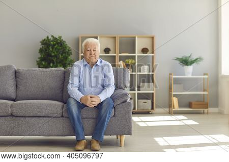 White-haired Senior Man Sitting Alone On Couch At Home And Thinking About His Life