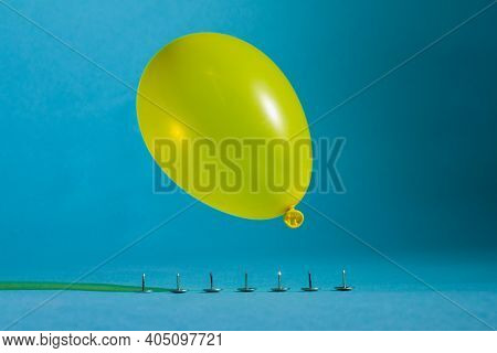 Yellow Balloon Drops Sharp Buttons. The Ball Will Burst From Piercing With Sharp Spikes