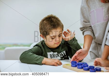Portrait Of Young Cute Boy With Down Syndrome Studding At School. Copy Space.