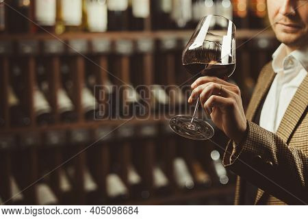Male Sommelier Tasting Red Wine At Cellar, Close-up Photo.