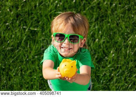 Child Holding Piggy Bank In Hands Against Green Spring Background. Fundraiser For Environmental Prot