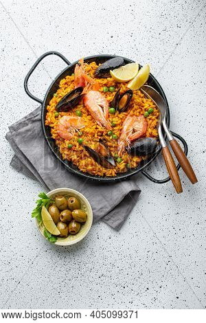 Classic Dish Of Spain, Seafood Paella In Traditional Pan On White Wooden Background Top View. Spanis