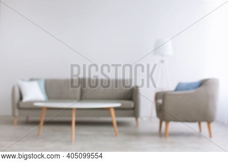 Blurred Photo Of Home Office And Living Room In Style Of Minimalism. Couch With White And Blue Pillo