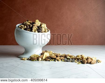White Raised Bowl Fill Of Trail Mix, Nuts And Dried Fruit Spilling Out Onto The Herringbone Counter