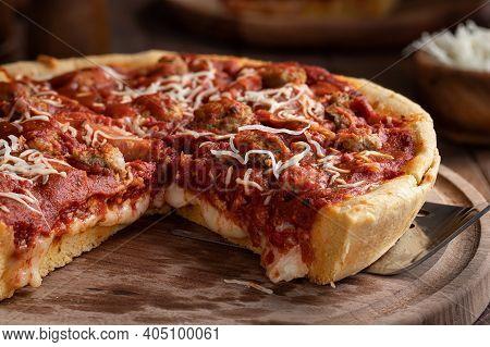 Closeup Of A Deep Dish Sausage Pizza On A Wooden Platter