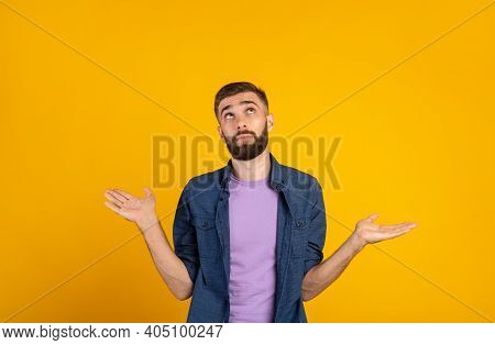 Who Knows. Confused Caucasian Guy Shrugging Shoulders On Orange Studio Background, Panorama. Uncerta