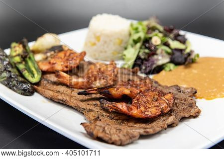 Grilled Carne Asada Steak Topped With Split Grilled Shrimp Served On A Plate With Rice And Beans.