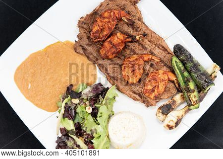 Overhead View Of Grilled Carne Asada Steak Topped With Split Grilled Shrimp Served On A Plate With R