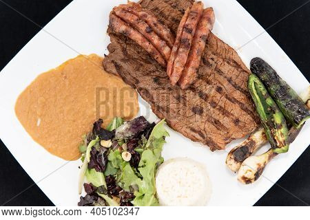 Overhead View Of Grilled Carne Asada Steak Topped With Chorizo Served On A Plate With Rice And Beans