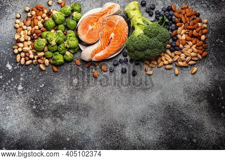 Assorted Food For Brain Health And Good Memory: Fresh Salmon, Vegetables, Nuts, Berries On Stone Bac