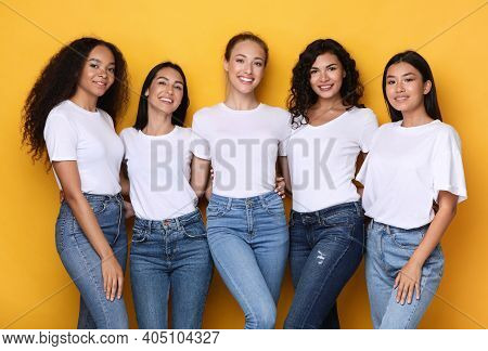 Group Of Five Diverse Models Ladies Posing Smiling To Camera Standing On Yellow Studio Background. M