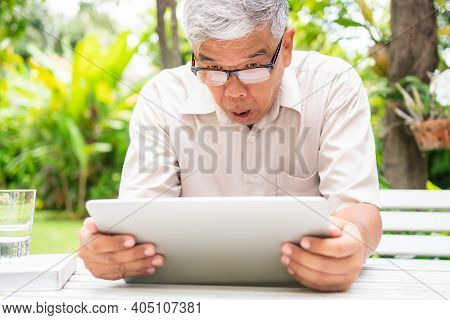 Portrait Of An Old Elderly Asian Man Is Holding A Computer Laptop And Surprised After Got Some Email
