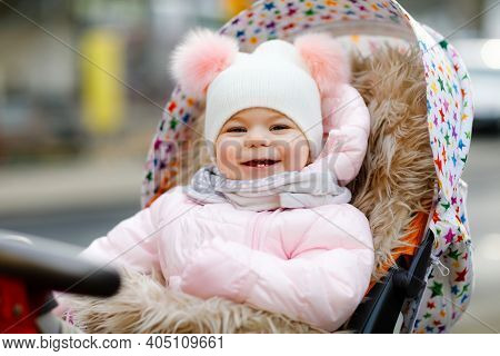 Cute Little Beautiful Baby Girl Sitting In The Pram Or Stroller On Cold Autumn, Winter Or Spring Day