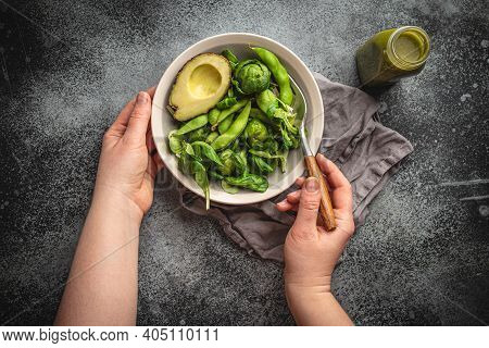 Bowl Of Healthy Salad In Female Hands From Above And Green Detox Smoothie In A Bottle On Gray Stone