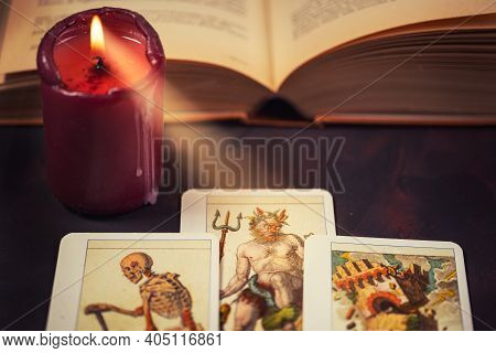 Tarot Cards With Candlelight And Book On The Darkness Background,halloween And Future Reading Concep