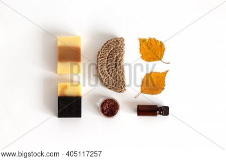 Soap, Jute Washcloth, Aromatic Oil, Towel Are Laid Out On A White Background. The Concept Of Cleansi