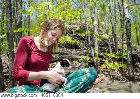 Portrait Of A Young Blonde Woman Sitting Cross Legged On A Rock In The Middle Of The Woodlands, With