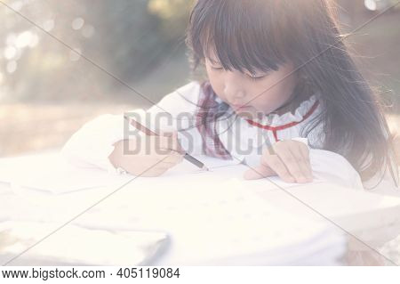 Asian Little Girl Lying Drawing Or Made Homework In The Paper Book For Preschool Kids In The Home Ga