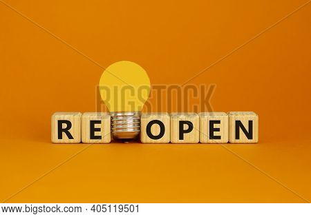 Reopen Symbol. Wooden Cubes With Word 'reopen'. Yellow Light Bulb. Beautiful Orange Background. Busi