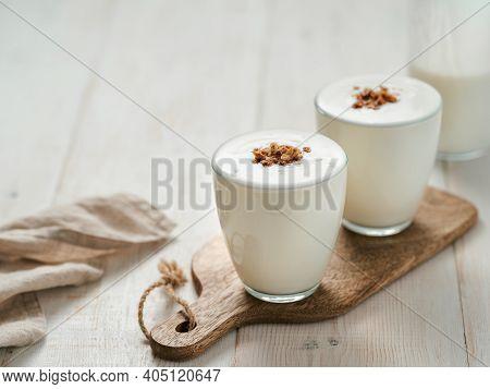 Kefir, Buttermilk Or Yogurt With Granola. Yogurt In Glass On White Wooden Background. Probiotic Cold