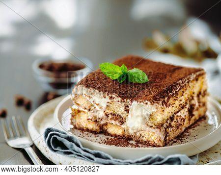 Perfect Homemade Tiramisu Cake With Fresh Mint. Tiramisu Portion On Plate Over Gray Background. Deli