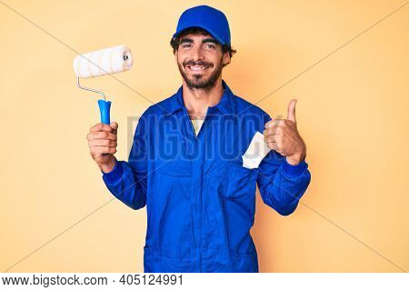 Handsome young man with curly hair and bear wearing builder jumpsuit uniform holding paint roller smiling happy and positive, thumb up doing excellent and approval sign