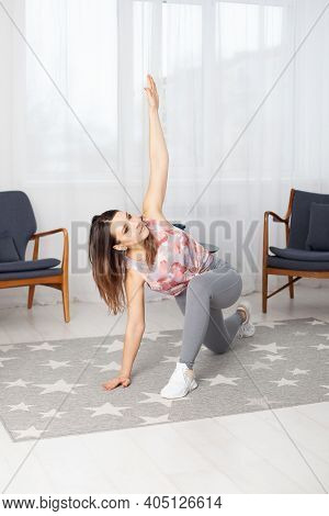 A Full-length Young Fit Woman In Gray Leggings With Her Legs Spread Wide Makes Twists In A Home Inte