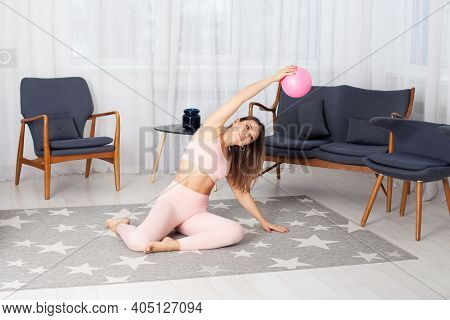 Beautiful European Woman In Pink Tracksuit Sits On The Floor And Does Sideways Bends With A Ball In