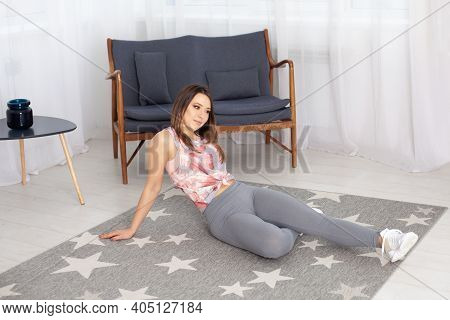 A Woman In Gray Leggings Sits In A Relaxed Pose On A Gray Carpet On The Floor In A Home Interior