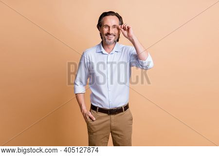 Photo Of Self-assured Mature Man Hold Eyeglasses Look Camera Wear Specs Shirt Isolated Beige Color B