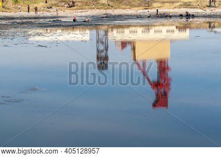 Sol-iletsk, Russia, 08.27.2020. Lake Tuzluchnoye. The Russol Salt Plant Is Reflected In The Black Wa
