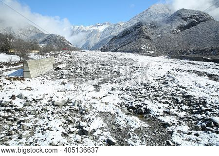 Winter And Mountains . There Is Fog At The Foot Of The Mountains . It Snowed On The River Stones. In