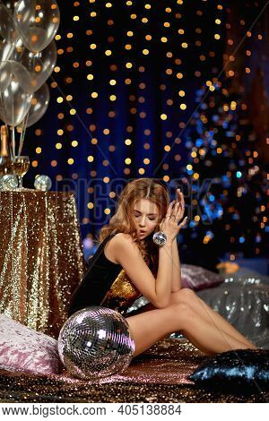 Beautiful Curly Blonde Woman In A Gold Sequins Party Dress Is Holding Mirror Ball. Glamour Model Pos