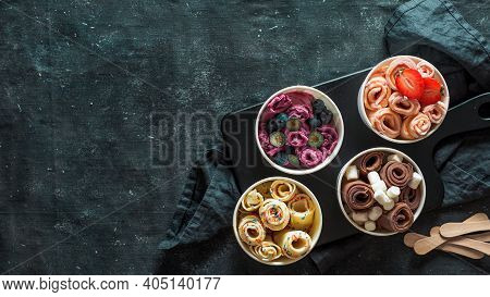 Rolled Ice Cream In Cone Cups On Dark Background. Different Iced Rolls Top View Or Flat Lay. Thai St