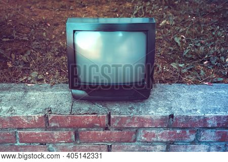 Toned Photo Of Old Analog Television Set On The Street Outdoor