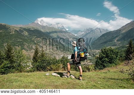 Hiker Man Stands On The Cliff Against The Top Of A Mountain. Man Has A Backpack And Trekking Poles.