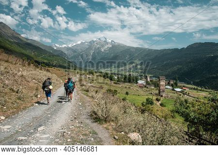Hiking. Trekking In Mountains. People With Backpacks In Mountain Trek. Tourists Hike To Mountain Pas