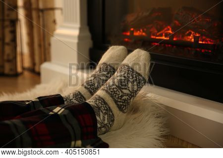 Woman In Warm Socks Sitting Near Fireplace With Burning Wood At Home, Closeup