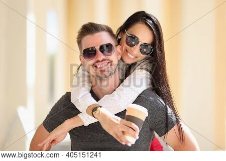 Smiling Woman In Sunglasses Holds Coffee And Hugs Man. Happy Harmonious Relationship Concept