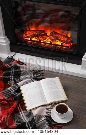 Cup Of Hot Coffee, Plaid And Book On Floor Near Fireplace, Above View. Cozy Atmosphere