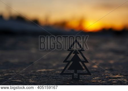 Horizontal Conceptual Close-up Photo With A Silhouette Of A Toy Christmas Tree Against Sunset Skylin