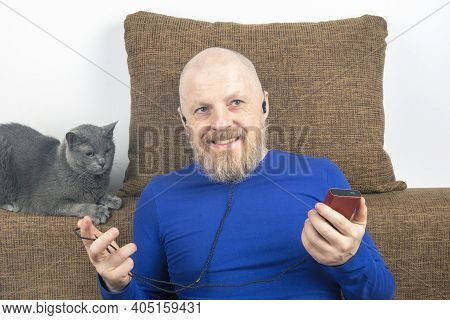 Bearded Man Enjoys Listening To His Favorite Music Through An Audio Player In Small Headphones. Audi
