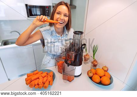 Happy Healthy Woman Making Fresh Carrot Juice In A Juicer In The Kitchen At Home. Juicer And Homemad