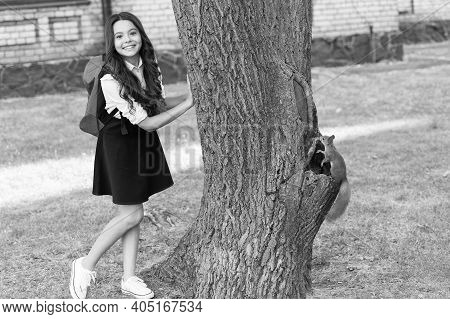 Studying Animal In Natural Environment. Little Child And Cute Squirrel Sitting At Tree. Animal Scien
