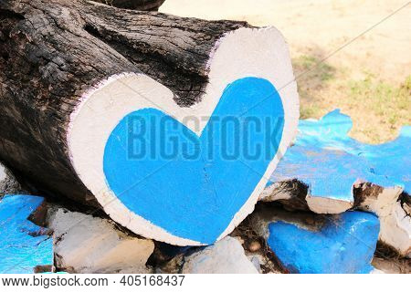 The Tree Trunk Is N The Shape Of A Heart, Painted With Blue And White Paint. A Blue Heart Is Painted