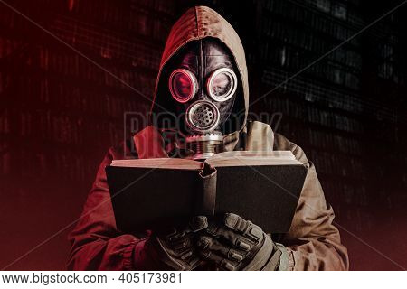 Photo Of Stalker Soldier In Soviet Gas Mask Holding Opened Old Book On Dark Background.