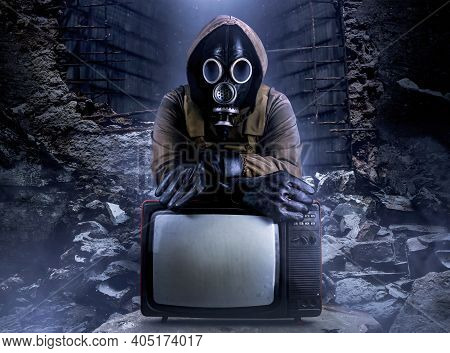 Photo Of Stalker Soldier In Jacket And Armored Vest And Rubber Gloves Standing With Old Tv Set On Ru