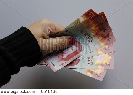 Hand Of A Woman Holding Mexican Banknotes Of 100 Pesos