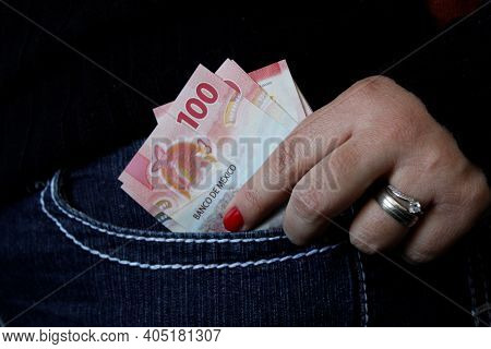 Hand Of A Woman Keeping Mexican Bills In Her Jeans