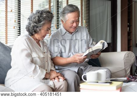 Happy Asian Senior Couple In Love Sitting On Sofa Reading A Book Together At Home. Cheerful Mature A